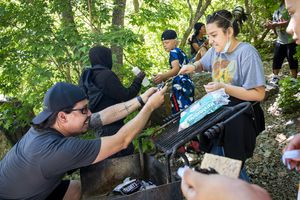 (Isaac Hale | Special to The Tribune) Sixth grade teacher John Arthur helps Marly Mendoza, 12, complete a s'more during an end-of-the-year field trip for Meadowlark Elementary School students in Big Cottonwood Canyon on Friday, June 4, 2021.