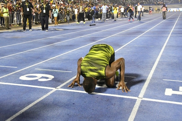 Jamaica's Usain Bolt kisses the track after winning the