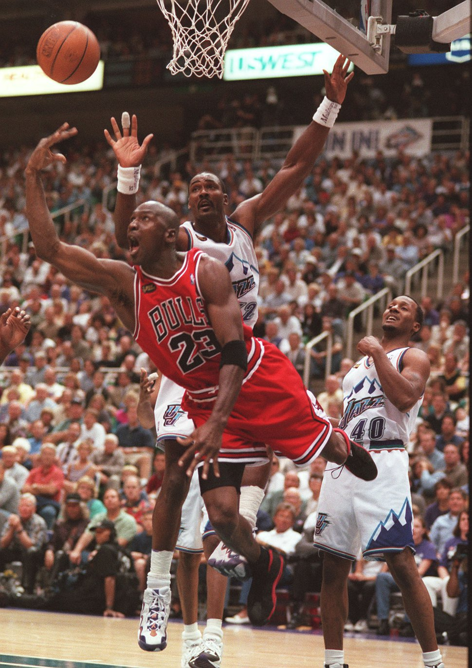 (Trent Nelson | Tribune file photo) Chicago Bulls guard Michael Jordan (23) attempts a shot going past Utah Jazz forward Karl Malone (32) during Game 1 of the 1998 NBA Finals at the Delta Center in Salt Lake City, June 3, 1998.