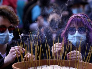 People leave incense sticks in a pot of rice to honor the victims of the Atlanta area massage parlors shootings during a memorial in Kansas City, Mo., Sunday, March 28, 2021. The March 17 shootings at three Georgia massage parlors and spas that left eight people dead, six of them women of Asian descent, come on the heels of a recent wave of attacks against Asian Americans since the coronavirus entered the United States. (AP Photo/Charlie Riedel)