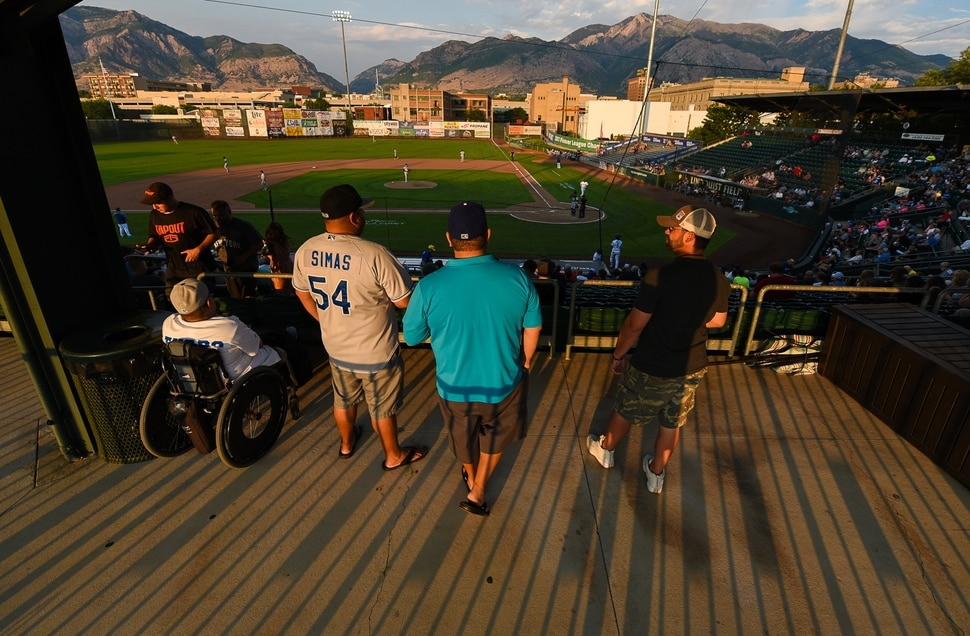 (Francisco Kjolseth | The Salt Lake Tribune) Spectators take in the game and views of the Wasatch Range as the sun sets on a Raptors baseball game at Lindquist Field in Ogden on Wed. July 25, 2018.