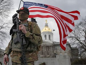(Winslow Townson | The Associated Press) An armed protester stands in front of the statehouse on Sunday, Jan. 17, 2021, in Concord, N.H.