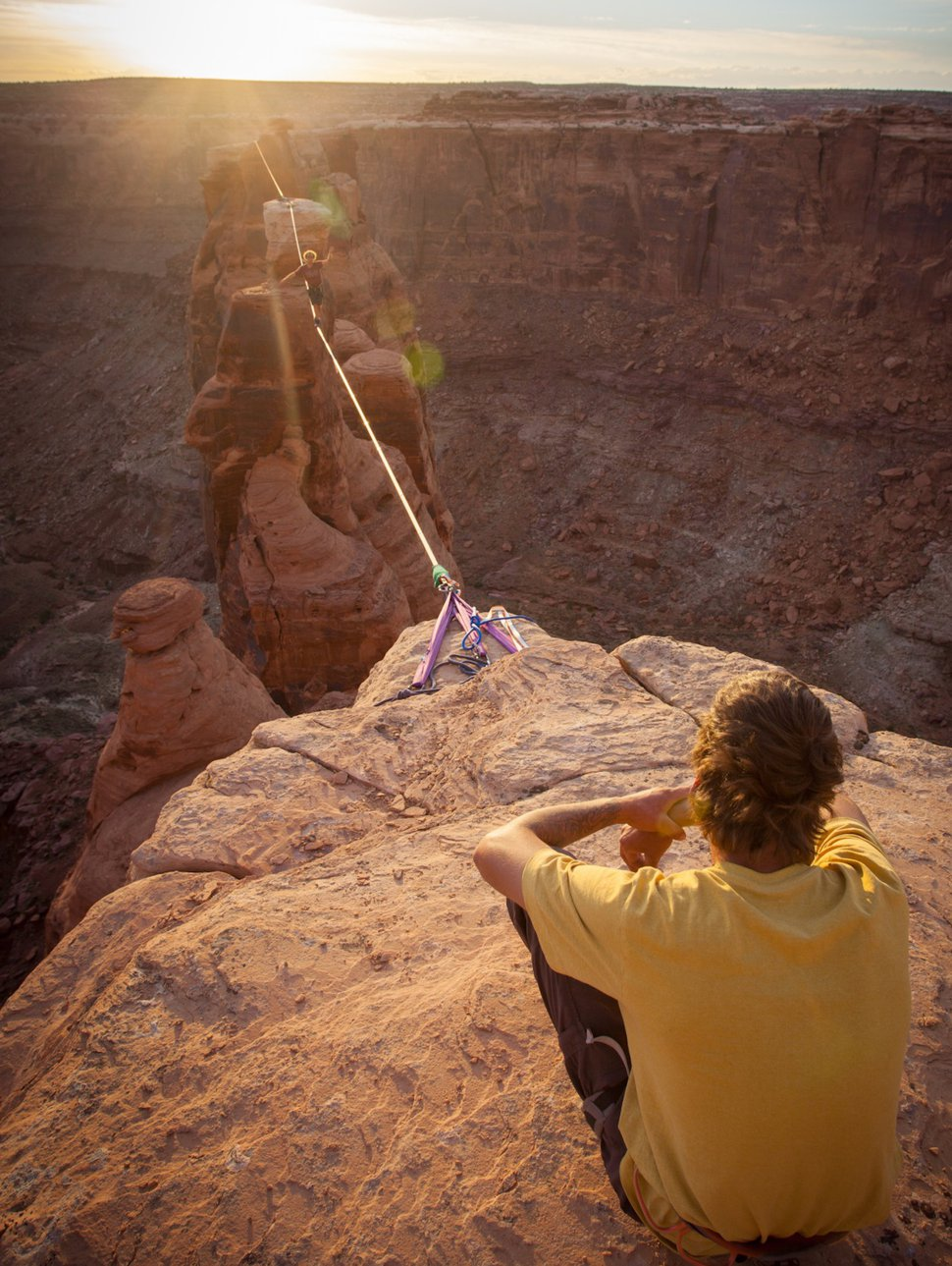 (Courtesy photo by BASE Jump Moab) An aerial athlete shuffles across a slackline between The Witch and The Warlock and the rim of Hell Roaring Canyon near Canyonlands National Park. Last April, Moab-based guide Andy Lewis and fellow