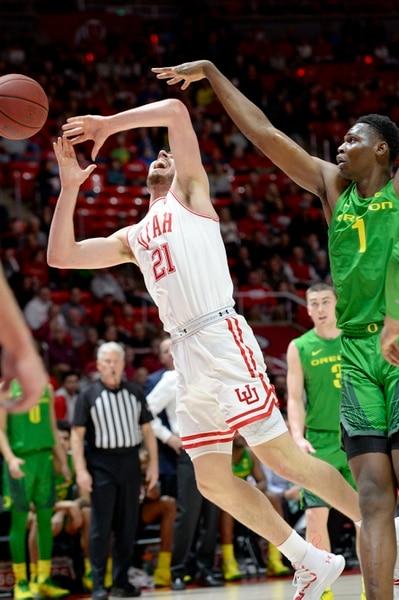 (Leah Hogsten | The Salt Lake Tribune) Utah Utes forward Riley Battin (21) is fouled by Oregon Ducks center N'Faly Dante (1) as the University of Utah basketball team hosts No. 4 Oregon, Jan. 4, 2020, at the Huntsman Center.