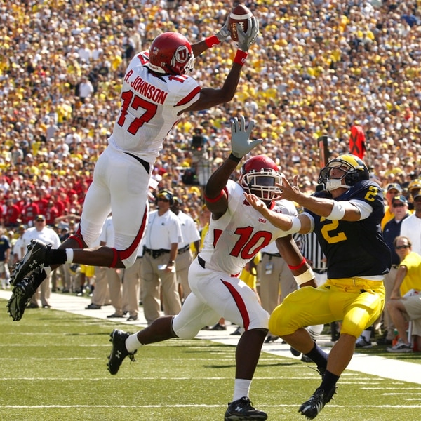 (David Guralnick | The Detroit News) Michigan's Sam McGuffie watches as Utah's Robert Johnson grabs what would have been an interception if teammate Stevenson Sylvester hadn't interfered with McGuffie. Photos are of the University of Michigan vs Utah at Michigan Stadium, August 30, 2008.