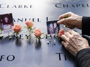 Mourners place flowers and pictures in the name cut-out of Kyung Hee (Casey) Cho at the National September 11 Memorial and Museum, Friday, Sept. 11, 2020, in New York. Americans commemorated 9/11 as a new national crisis in the form of the coronavirus pandemic reconfigures and divides anniversary ceremonies and a presidential campaign carves a path through the observances. (AP Photo/John Minchillo)