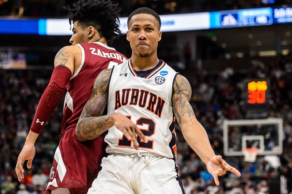 (Trent Nelson | The Salt Lake Tribune) Auburn Tigers guard J'Von McCormick (12) plays air guitar to celebrate a basket as Auburn faces New Mexico State in the 2019 NCAA Tournament in Salt Lake City on Thursday March 21, 2019.