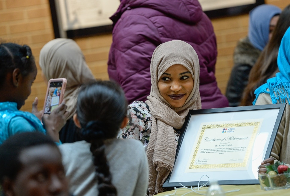 (Francisco Kjolseth | The Salt Lake Tribune) Masagid Abdalla a refugee from Sudan has her picture taken with her new award of achievement during the Women of the World 8th annual award ceremony at the Salt Lake County building in Salt Lake City on Saturday, Dec. 8, 2018. The event is a celebration of successes including educational, service, and employment milestones by refugee women.