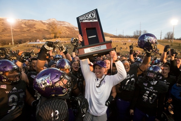Weber State coach Jay Hill hoists the Big Sky championship trophy after his team defeated Idaho State 35-7 in an NCAA college football game Saturday, Nov. 18, 2017, in Ogden, Utah. Weber State won a share of the conference title. (Matt Herp/Standard-Examiner via AP)