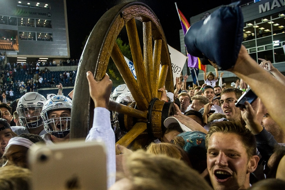 (Chris Detrick   The Salt Lake Tribune) Utah State Aggies football players and students celebrate with the Old Wagon Wheel after the game at Merlin Olsen Field at Maverik Stadium Friday, September 29, 2017. Utah State Aggies defeated Brigham Young Cougars 40-24.