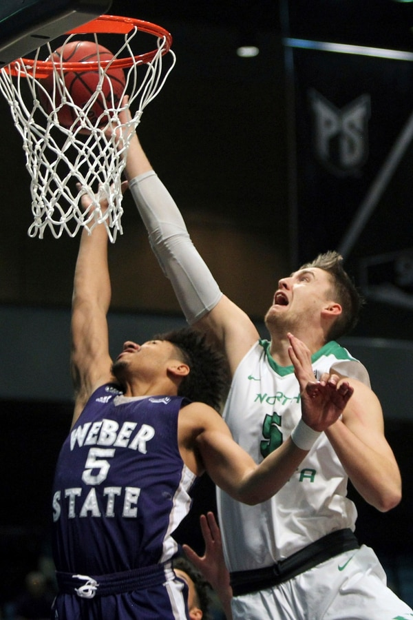 North Dakota center Carson Shanks (5) shoots in front of Weber State guard Cody John (5) during the first half an NCAA college basketball game in the finals of the Big Sky tournament in Reno, Nev., Saturday, March 11, 2017. (AP Photo/Lance Iversen)