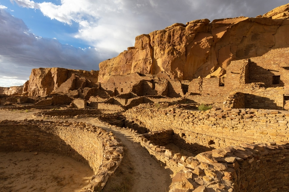 """Pueblo Bonito, the largest and grandest of the 12 """"great houses,"""" at the Chaco Culture National Historic Park in northwestern New Mexico, on Sept. 2, 2019. In the red rock desert of the Southwest, an ancient culture was thought to have vanished but a new view connects it to pueblo dwellers of today. (John Burcham/The New York Times)"""