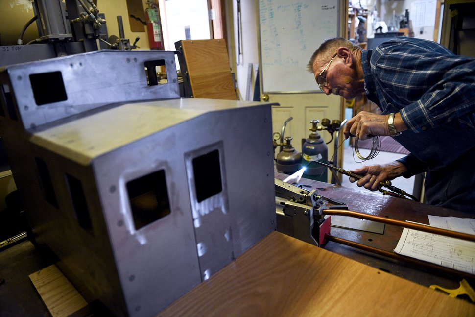 ADVANCE FOR USE WITH WEEKEND EDITIONS JULY 7-8, 2018 AND THEREAFTER In this Tuesday, June 19, 2018, photo, Jim Smeltzer welds a miniature ladder that will eventually attach to the back of the caboose in his workshop at his home in Highland. Since 2004, the Smeltzers' land surrounding their home has been a model railyard. (Isaac Hale/The Daily Herald via AP)