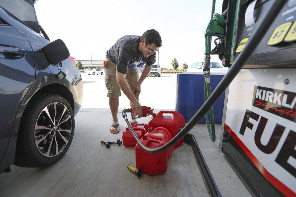 (Steve Gonzales | Houston Chronicle via AP) Chris Mathew fills his vehicle and five gas cans at Costco in preparation for tropical weather on Wednesday, Aug. 23, 2017, in Pearland, Texas. The U.S. National Hurricane Center said the tropical depression was expected to intensify over the warm waters of the Gulf of Mexico before reaching the Texas coast Friday.