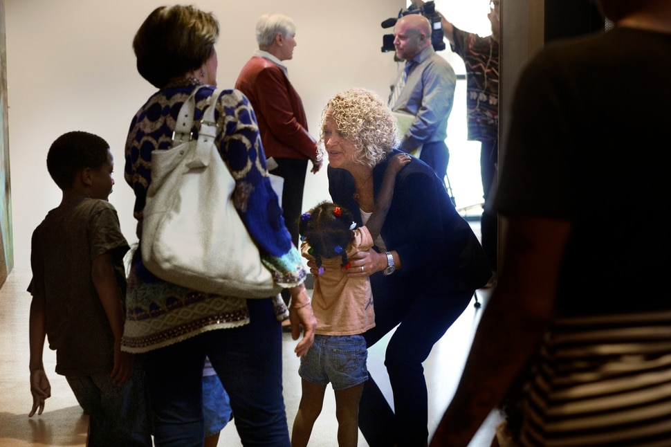 (Scott Sommerdorf | The Salt Lake Tribune) Salt Lake City Mayor Jackie Biskupski reaches down to pick up a member of the Tillman family who had come to the VOA, Utah Homeless Youth Resource Center to visit a family member. Mayor Biskupski was there to speak at a press conference where it was announced that Gail Miller and the Miller family after had made a challenge grant of up to 10 million dollars to fund future homeless programs and services at the VOA, Utah Homeless Youth Resource Center, Thursday, August 17, 2017.