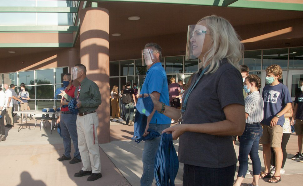 (Chris Caldwell | The Spectrum and Daily News) Faculty members at Snow Canyon High School distribute masks to students on the first day of class in Washington County School District Thursday, Aug. 13, 2020.