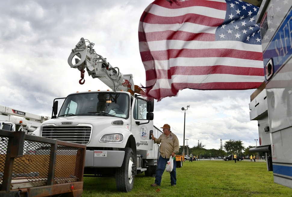 (Mike Lang | Sarasota Herald-Tribune | The Associated Press) An employee of Southern Electric Corporation from Flowood, Miss., climbs out of the cab of his truck after arriving at the Sarasota Fairgrounds Tuesday, Oct. 9, 2018. Florida Power & Light is staging their power restoration contractors in Sarasota, Fla., in advance of Hurricane Michael's expected landfall in the Florida panhandle later this week.