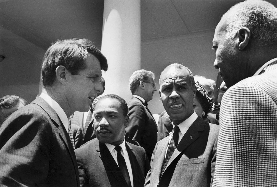 FILE - In this June 22, 1963, file photo, U.S. Attorney General Robert F. Kennedy, left, speaks with civil rights leaders, beginning second from left, the Rev. Martin Luther King Jr., head of the Southern Christian Leadership Conference; Roy Wilkins, executive secretary of the NAACP; and A. Phillip Randolph, president of Brotherhood of Sleeping Car Porters, on the White House grounds in Washington, D.C. Civil rights lawyer Joseph Rauh stands in the background at center. Nearly 50 years after Kennedy's assassination, a new documentary series on his life and transformation into a liberal hero has come to Netflix.