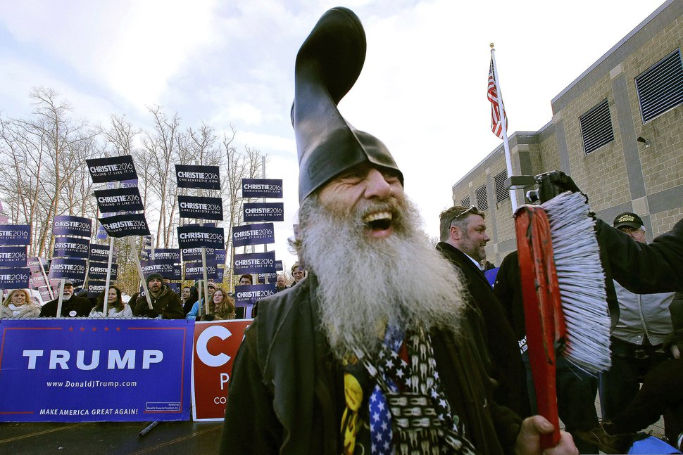FILE - In this Tuesday, Feb. 9, 2016, file photo, satirical Democratic presidential candidate Vermin Supreme smiles while holding a giant toothbrush with a boot on his head during a campaign stop at a polling station on primary election day in Londonderry, N.H. The performance artist said he is mounting a write-in campaign as a Democrat candidate for the U.S. Senate in Massachusetts in the Tuesday, Sept. 1, 2020, primary election. (AP Photo/Charles Krupa, File)