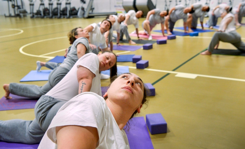 Leah Hogsten | The Salt Lake Tribune Misty Hill, center, holds a pose as yoga instructor apprectice Ferosa Bluff, right, leads a yoga class at the Timpanogos WomenÕs Correctional Facility gymnasium at the Utah State Prison. ÒYou can have a positive experience in a place that is known for a negative connotation, said Bluff. Even in a place like this we can find the beauty and peace in something like yoga.