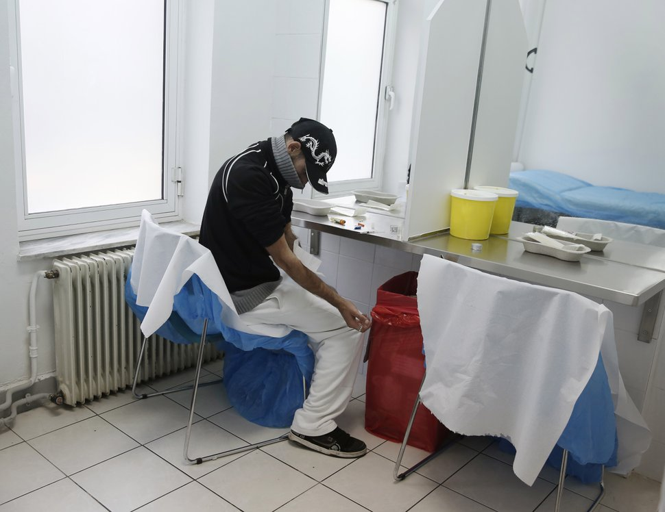 (Petros Giannakouris | AP file photo) In this 2013 photo, A drug user cleans his arm at a supervised injection site in central Athens. Drug experts and policy makers from around Europe gathered in Athens to urge their governments to exclude drug treatment from economic austerity programs, citing an alarming rise in HIV infections among drug users in Greece. The number of reported new infections among drug users in Greece shot up from 22 in 2010 to 245 in 2011, according to the European Centre for Disease Prevention and Control. Experts blame the rise on a number of factors, several related to Greece's major financial crisis.