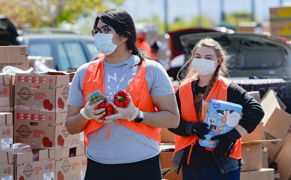 (Francisco Kjolseth   The Salt Lake Tribune) Volunteers Jiazhen Priest, left, and Maddie McDougal help out as the Utah Food Bank does a big food giveaway at the Maverik Center in West Valley City on Friday, April 24, 2020, as hundreds line up for drive-thru pick up.