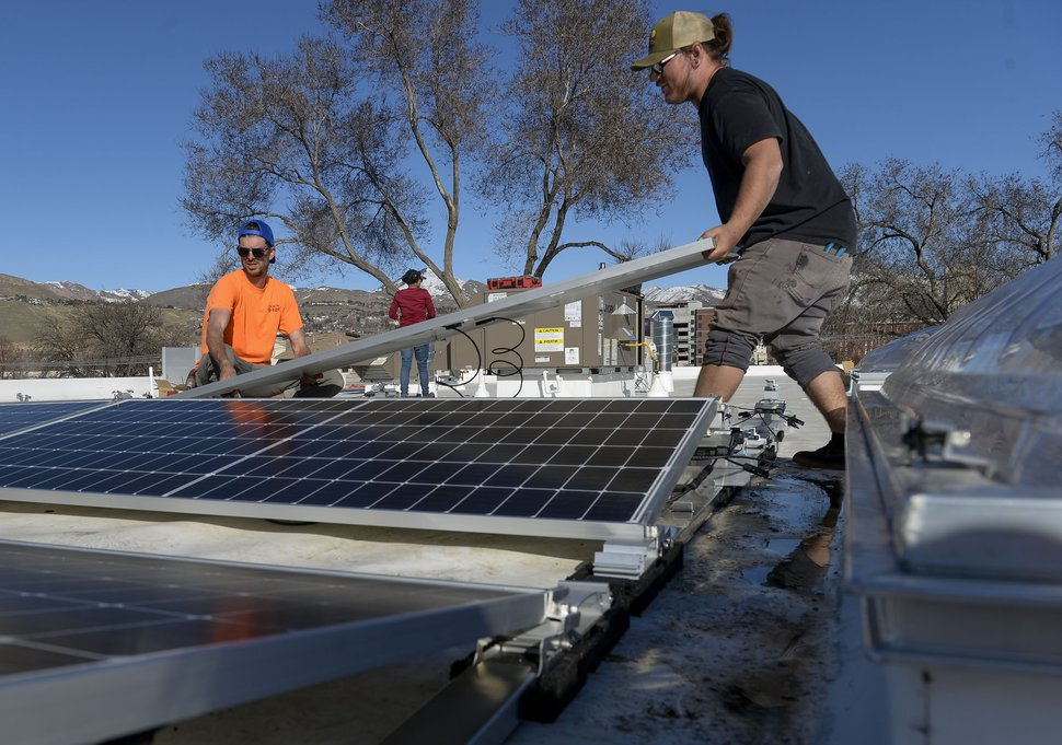 (Leah Hogsten | The Salt Lake Tribune) Creative Energies solar installation employees install photovoltaic panels on the roof of the Boys and Girls Club in Salt Lake City, March 5, 2020.