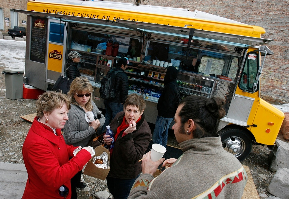 (Scott Sommerdorf | Salt Lake Tribune) Customers (left to right) Jennifer Baumgartner, Pat Aoyagi, Mitzi MacKay, and Sweeney Windchief (all cq) sample some home-made chips from the Chow Truck after they picked up their completed order. The Chow Truck is a bright yellow food truck that serves gourmet tacos and sliders. The owners are SuAn Chow (the original owner of Charlie Chows) and chef Rosanne Ruiz (Capital Cafe, Sage's Cafe and Vinto)