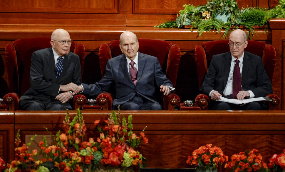 (Leah Hogsten | The Salt Lake Tribune) President Russell M. Nelson, center, reaches out to squeeze the hand of President Dallin H. Oaks, left, during the morning session of the189th Annual General Conference of The Church of Jesus Christ of Latter-day Saints in Salt Lake City. President Henry B. Eyring is at right.