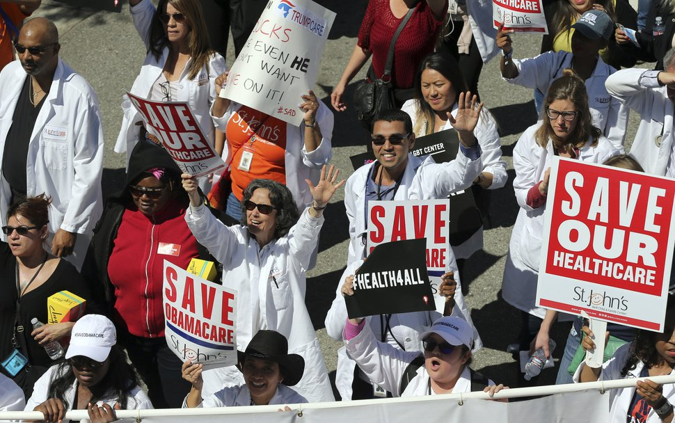 File - In this March 23, 2017, file photo, health care professionals join hundreds of people marching through downtown Los Angeles protesting President Donald Trump's plan to dismantle the Affordable Care Act. (AP Photo/Reed Saxon, File)