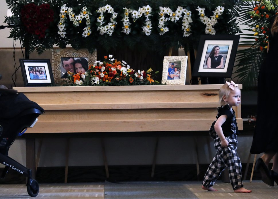 A child walks past a coffin that contain the remains of Christina Langford Johnson the last victim of a cartel ambush that killed nine American women and children earlier this week, in Colonia Le Baron, Mexico, Saturday, Nov. 9, 2019. In the attack Monday, Langford Johnson jumped out of her vehicle and waved her hands to show she was no threat to the attackers and was shot twice in the heart, community members say. Her daughter Faith Marie Johnson, 7 months old, was found unharmed in her car seat. (AP Photo/Marco Ugarte)