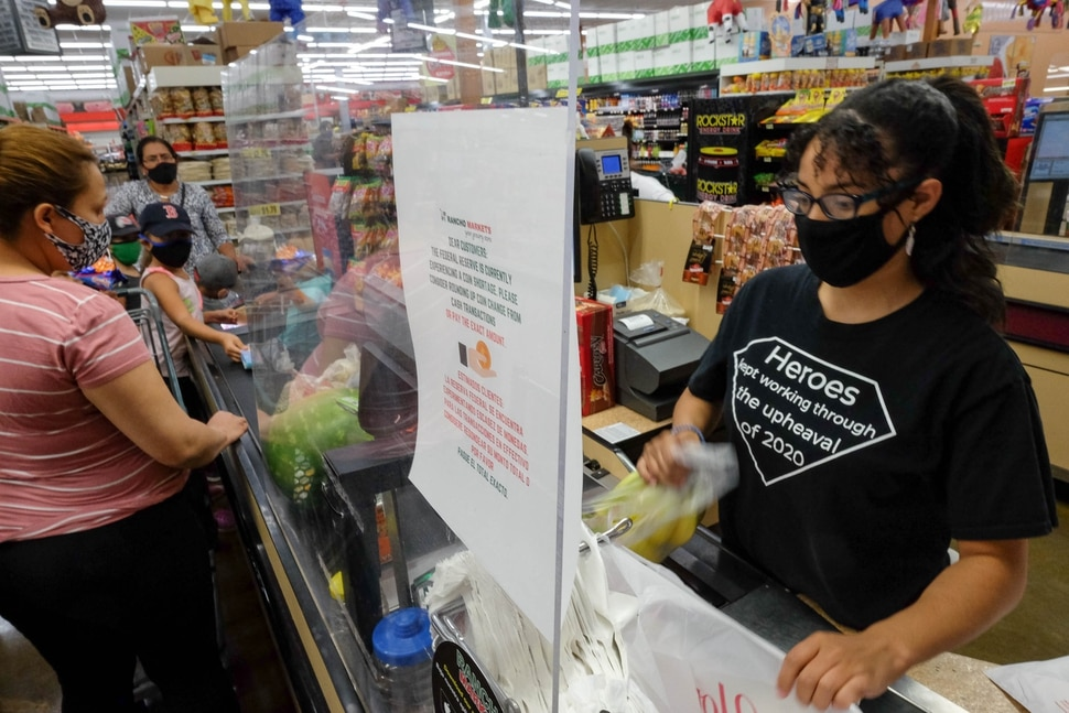 (Francisco Kjolseth | The Salt Lake Tribune) Yuderca Rosario checks people out from behind a plexiglass wall as Rancho Markets implement numerous safety precautions at their stores to navigate the coronavirus pandemic as people shop at the 140 N. 900 West location in Salt Lake City on Friday, August 14, 2020.