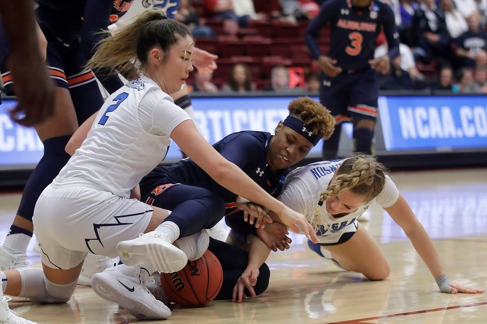 Auburn guard Daisa Alexander, center, reaches for the ball between BYU guard Shaylee Gonzales, left, and guard Paisley Johnson during the first half of a first-round game in the NCAA women's college basketball tournament in Stanford, Calif., Saturday, March 23, 2019. (AP Photo/Jeff Chiu)