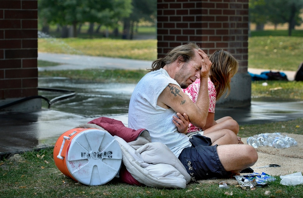 (Scott Sommerdorf | The Salt Lake Tribune) Homeless couple Daniel White and Angela Nuhl sit together in Fairmont Park after getting some bottled water from Volunteers of America workers who were in the park checking on campers, Wednesday, September 6, 2017.