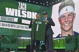(David Dermer | AP) BYU quarterback Zach Wilson, right, holds a team jersey with NFL Commissioner Roger Goodell after the New York Jets selected Wilson with the second pick in the first round of the NFL football draft Thursday, April 29, 2021, in Cleveland.