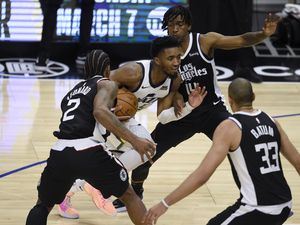 Utah Jazz guard Donovan Mitchell drives the ball between Los Angeles Clippers forward Kawhi Leonard, left, and guard Terance Mann, rear, during the second half of an NBA basketball game in Los Angeles, Friday, Feb. 19, 2021. (AP Photo/Kelvin Kuo)