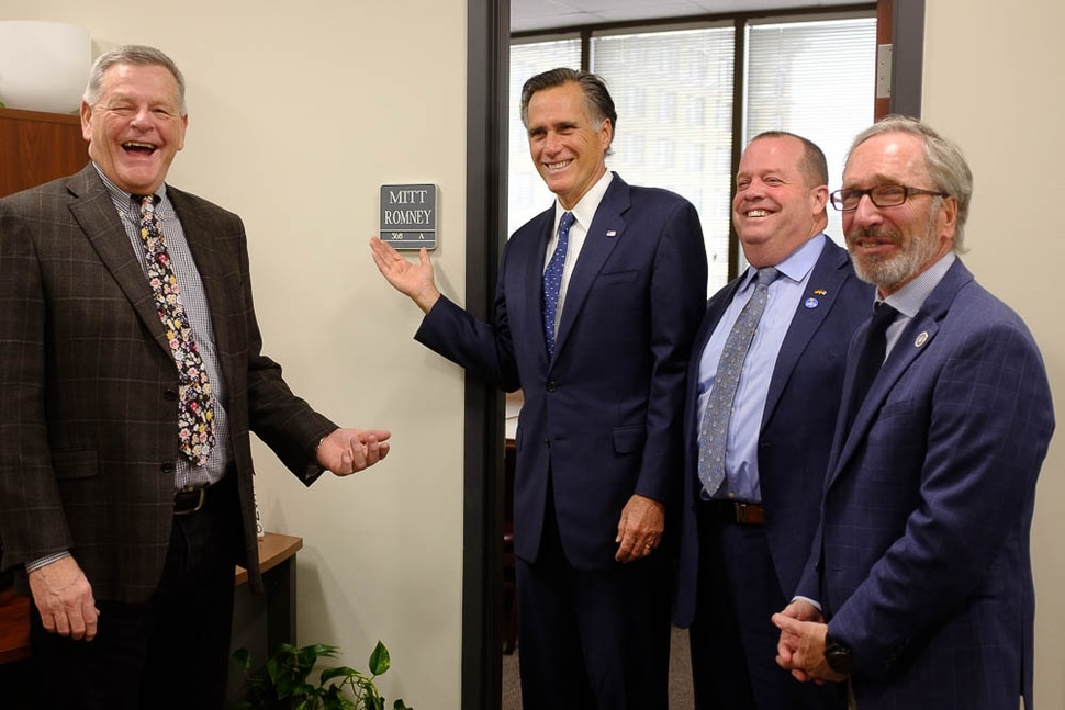 (Trent Nelson | The Salt Lake Tribune) Senator Mitt Romney poses in front of a conference room bearing his name after meeting with Weber County Comissioners in Ogden to discuss the ongoing government shutdown on Friday Jan. 18, 2019. From left, Commissioner Scott Jenkins, Romney, Commissioner James Harvey, and Commissioner Gage Froerer.