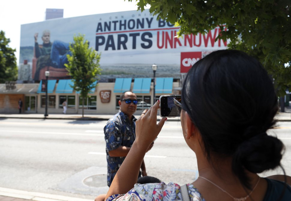 A woman takes a photograph of a billboard for the CNN television show