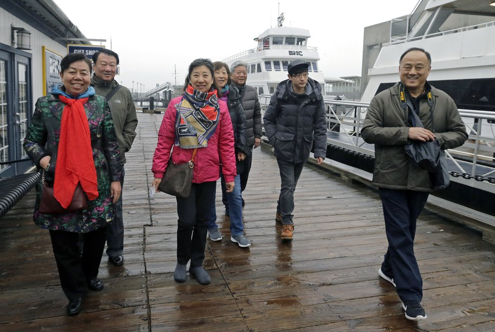 In this March 27, 2017, photo, tourists from China walk to board a boat for a harbor tour in Boston. In cities across the country, the American hospitality industry is stepping up efforts to make Chinese visitors feel more welcome. (AP Photo/Elise Amendola)