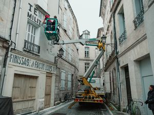 """In a photo provided by Roger Do Minh, The crew paints signs on building walls for shots in the Wes Anderson film.  For """"The French Dispatch,"""" the filmmakers set up shop in a real French city to create the setting for the movie's fictional one. (Roger Do Minh via The New York Times)"""