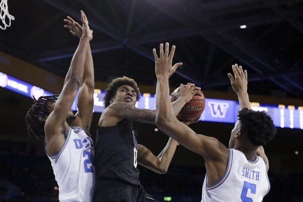 Washington forward Jaden McDaniels, middle, drives between UCLA forward Jalen Hill, left, and guard Chris Smith during the second half of an NCAA college basketball game in Los Angeles, Saturday, Feb. 15, 2020. (AP Photo/Chris Carlson)