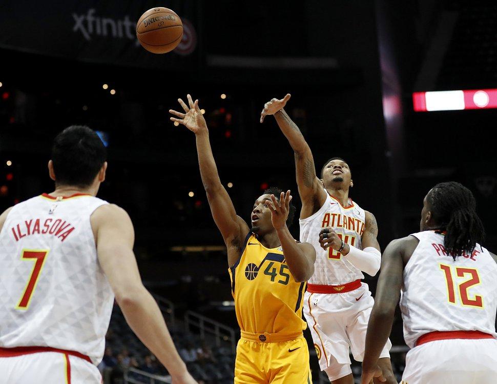 Utah Jazz's Donovan Mitchell (45) puts up a shot in front of Atlanta Hawks' Kent Bazemore in the first quarter of an NBA basketball game in Atlanta, Monday, Jan. 22, 2018. Atlanta won 104-90. (AP Photo/David Goldman)