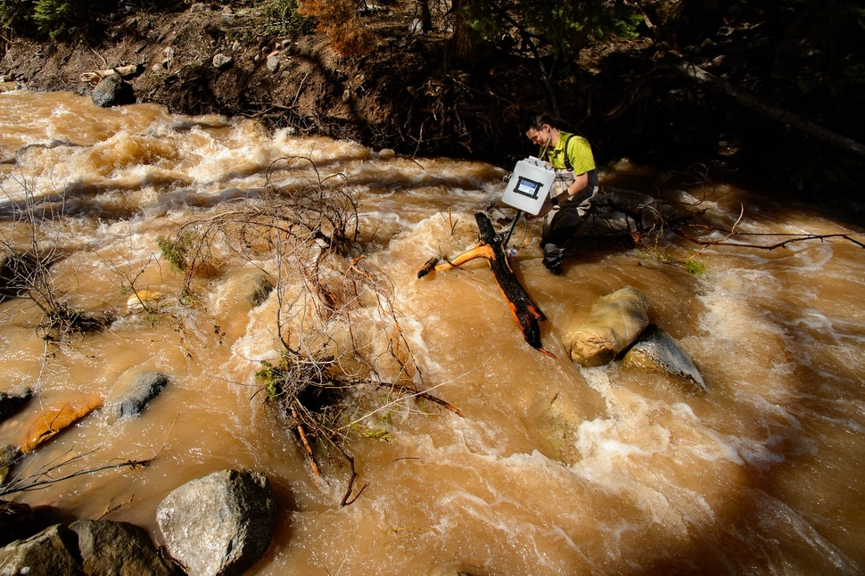 (Trent Nelson | The Salt Lake Tribune) Ben Abbott, Assistant Professor of Ecosystem Ecology at BYU, checks the status of a water monitoring station on Peteetneet Creek in Payson Canyon on Thursday April 25, 2019.