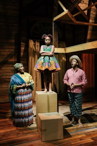 """(Photo courtesy of Pioneer Theatre Company) Cicily Daniels as Mama Euralie, Ava Lynn Smith as Little Girl/young Ti Moune and Derrick Cobey as Tonton Julian in PTC's production of """"Once On This Island."""""""