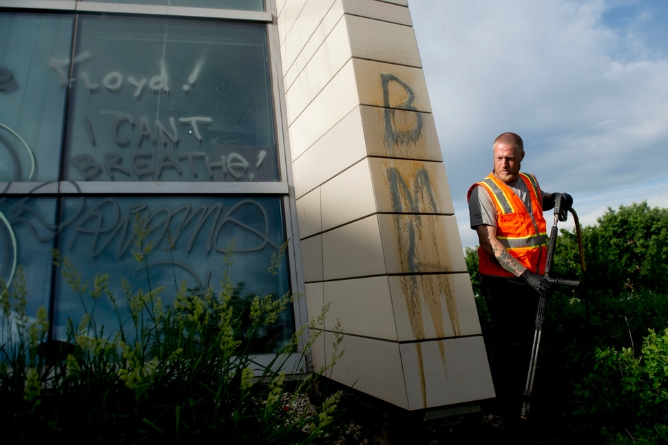 (Jeremy Harmon | The Salt Lake Tribune) Greg Hualde cleans graffiti off the Public Safety Building in Salt Lake City on Sunday, May 31, 2020.