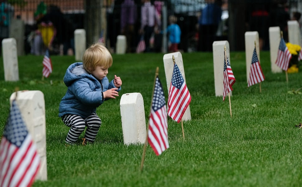 (Francisco Kjolseth | The Salt Lake Tribune) Leo Wilson participates in the adopted family tradition of placing a penny on top of military grave stones, during a Memorial Day ceremony at Fort Douglas cemetery on Monday, May 27, 2019.