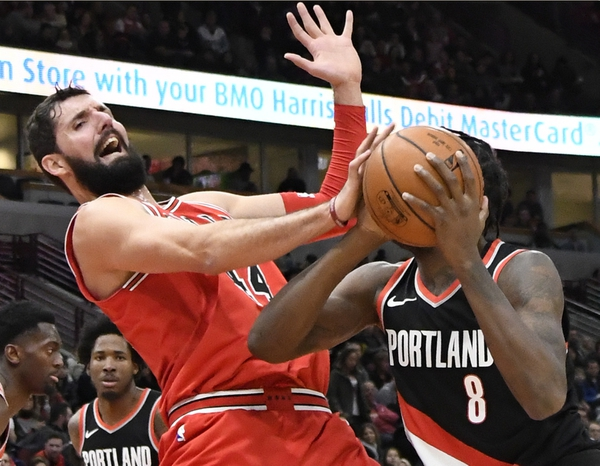 FILE- In this Jan. 1, 2018, file photo, Chicago Bulls forward Nikola Mirotic, left, defends against Portland Trail Blazers forward Al-Farouq Aminu (8) during the second half of an NBA basketball game in Chicago. A person familiar with the decision says the New Orleans Pelicans have acquired forward Nikola Mirotic and a second-round draft pick from the Chicago Bulls for center Omer Asik, guards Jameer Nelson and Tony Allen, and a future first-round pick. The person spoke to The Associated Press on condition of anonymity Thursday, Feb. 1, 2018, because neither team has announced the trade. (AP Photo/David Banks, File)