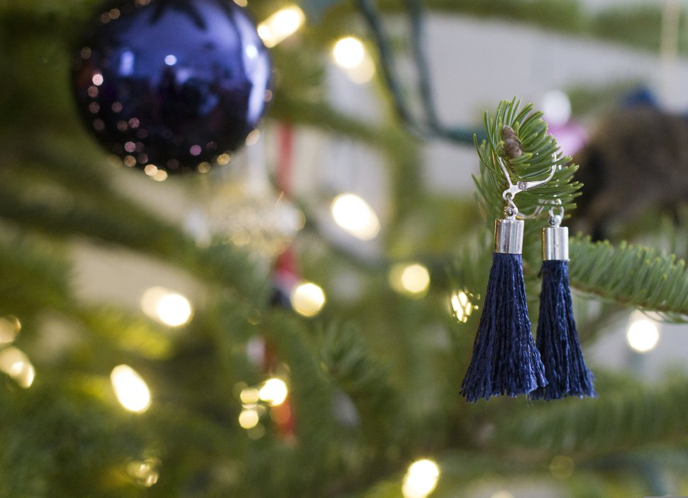 This Dec. 17, 2018 photo shows handmade earrings hanging on a Christmas tree in Hopkinton, N.H., which make for inexpensive stocking stuffers. This pair shown here are made from fringe trim more commonly used on pillows and other home goods. (AP Photo/Holly Ramer)