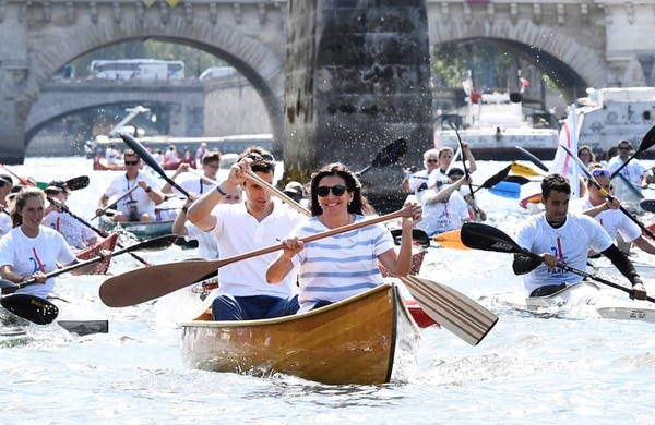 Paris Mayor Anne Hidalgo, front, and the co-president of the Paris bid for the 2024 Olympics Tony Estanguet paddle on the Seine river in Paris Friday, June 23, 2017. Paris is aiming to boost its bid for the 2024 Olympics by turning some of its world-famous landmarks over to sports for two days, with 100-meter races on a track floating on the Seine, high-diving into the river, cycling around the Arc de Triomphe and other events to showcase the French capital's suitability for the games. (Martin Bureau, Pool via AP)