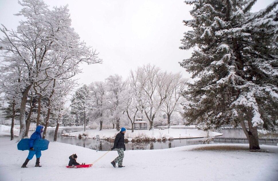 (Rick Egan | The Salt Lake Tribune) Jenda Michl pulls 4-year-old Mason Michl on a sled along as Mason's Grandfather Joseph follows behind, at Liberty Park, Friday, Nov. 29, 2019.